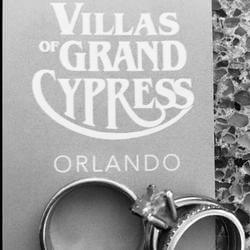 two wedding rings up against a grand cypress sign