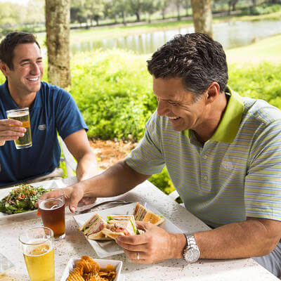 two men drinking and dining outside grand cypress