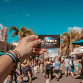 person holding universal ticket in front of theme park