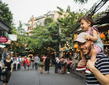 dad with daughter on shoulders at market