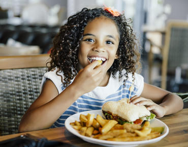 young girl eating a burger and fries and smiling