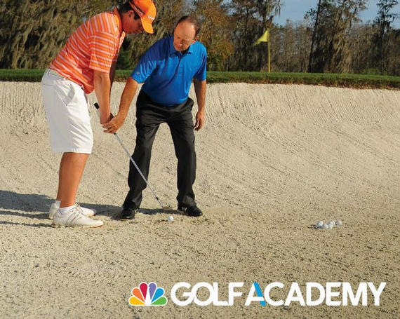 man teaching another man how to hit a golf ball out of the bunker