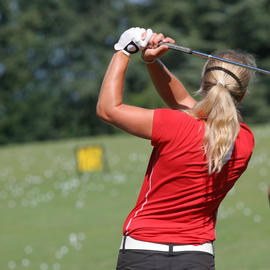 woman in her backswing on the golf course