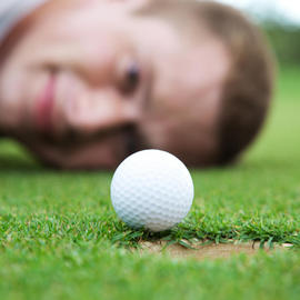 man looking at a golf ball go into the hole