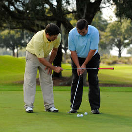 man coaching another man how to putt