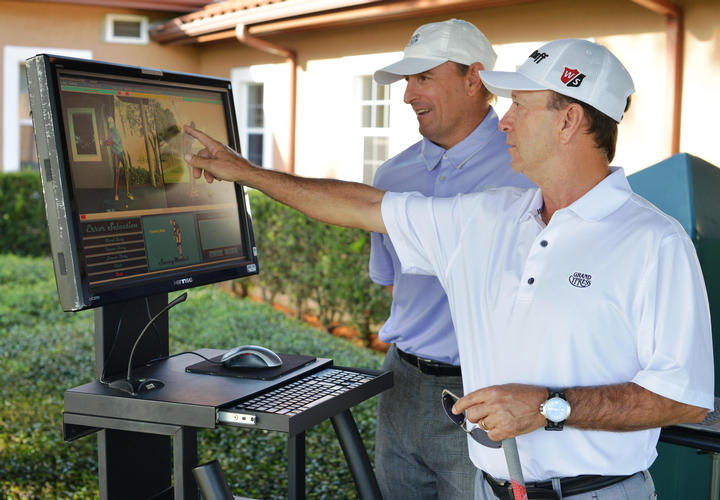 two men looking at their golf swing on a computer
