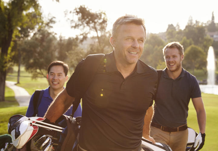 three men walking on the golf course