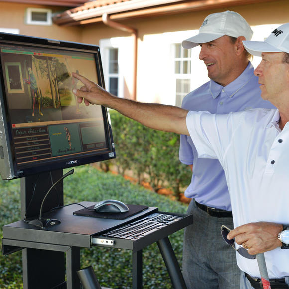 two men looking at their golf swings on a computer