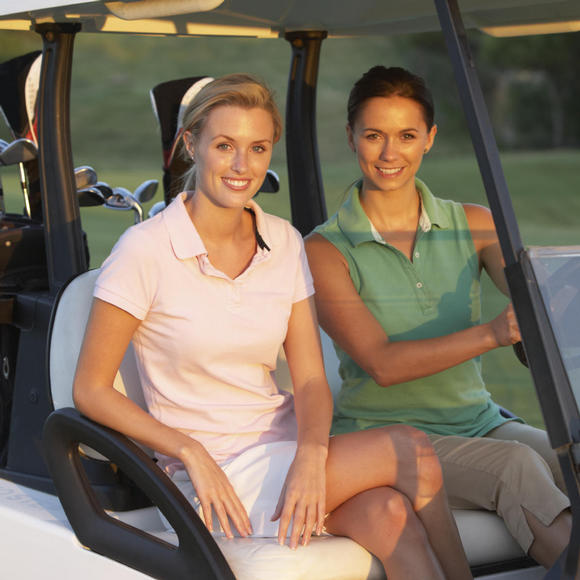 two women riding a golf cart at grand cypress