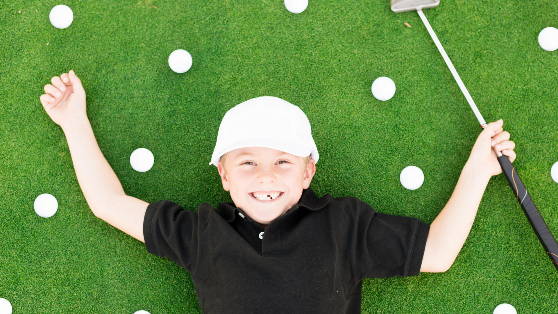 child lying on a green surrounded by golf balls
