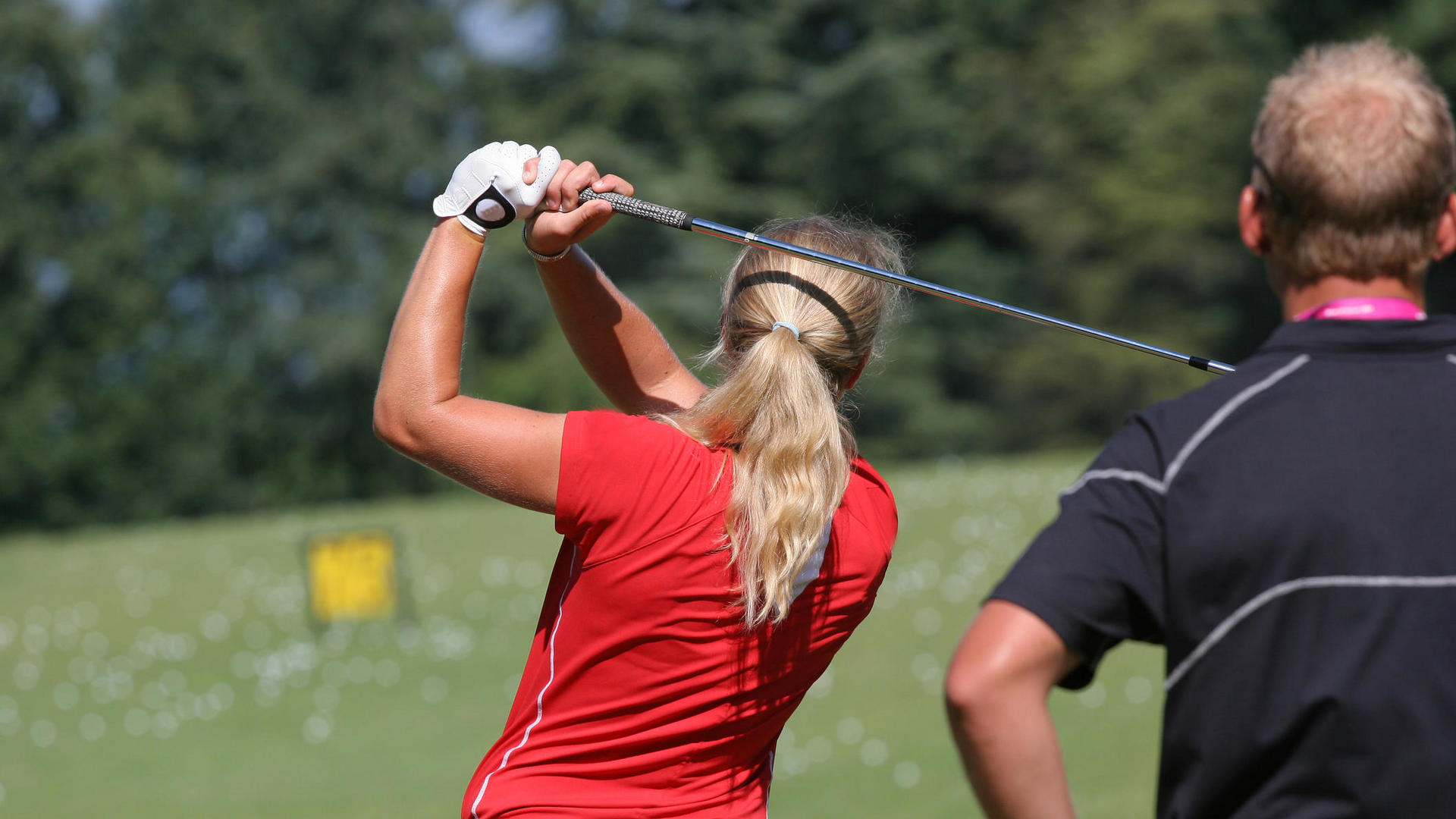 woman in her backswing while playing golf