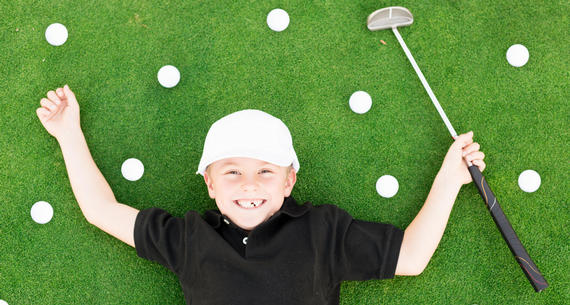 little boy lying on green surrounded by golf balls